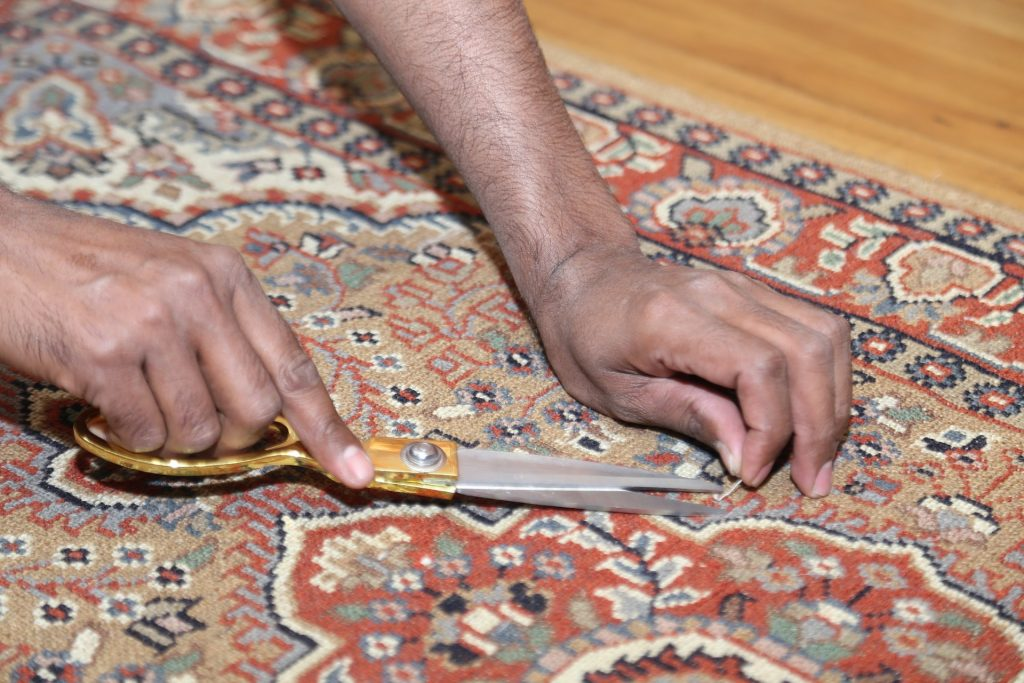 A person uses scissors to trim a loose piece of carpet after DIY carpet cleaning without a machine.