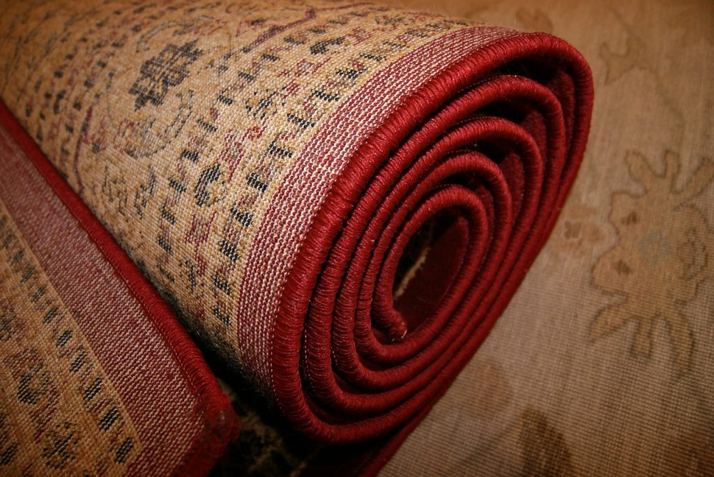 A rolled up carpet that needs DIY carpet cleaning without a machine.