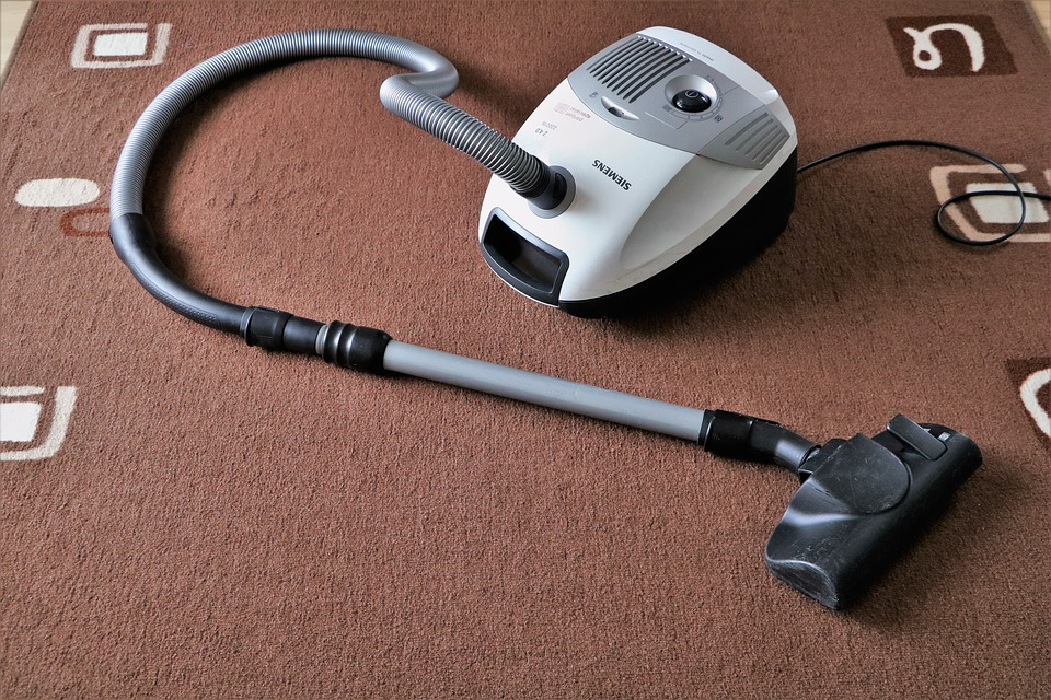 white vacuum cleaner in a carpeted floor